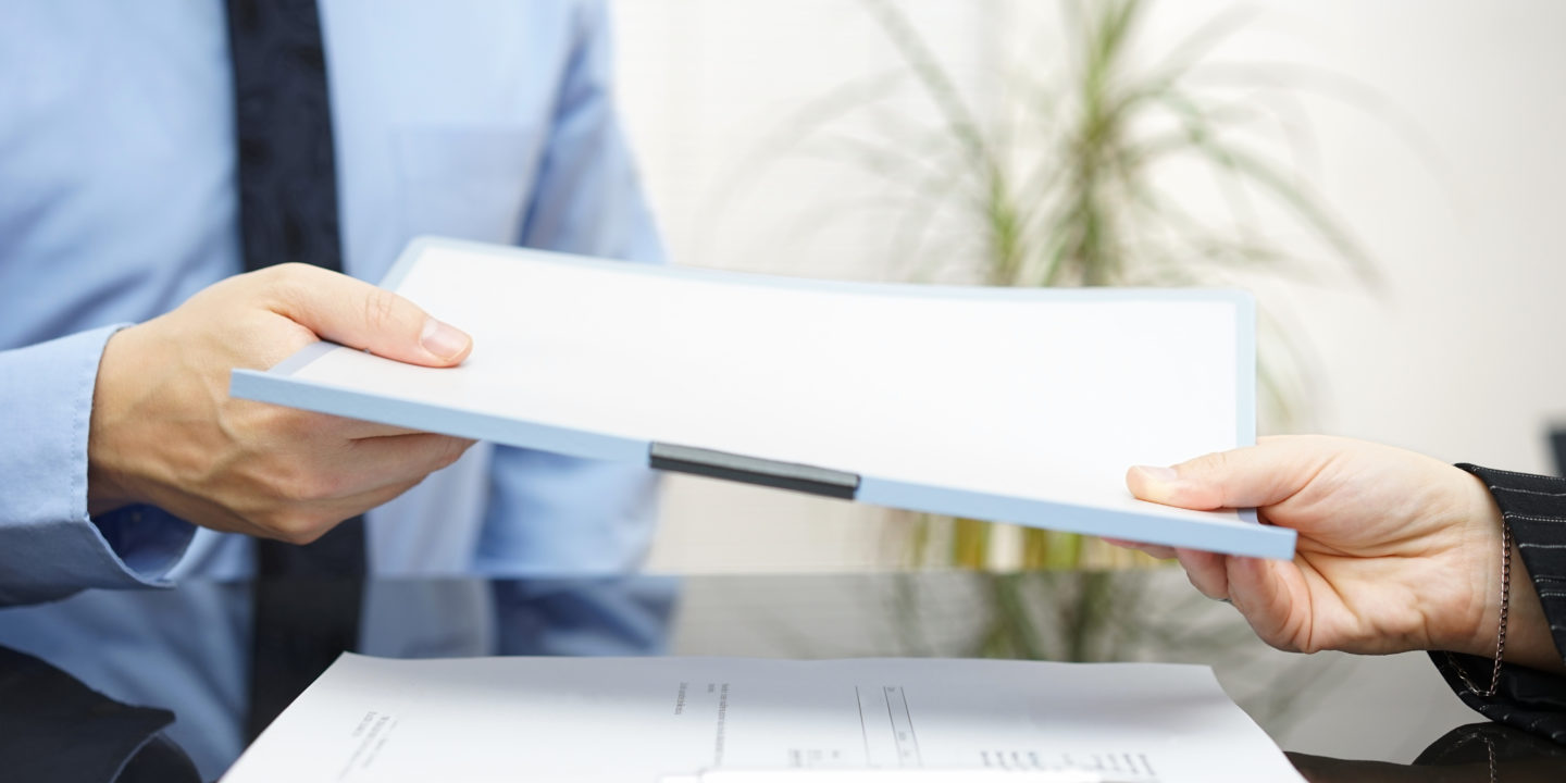 Two People Exchanging Documents - Standards Development | NSF International