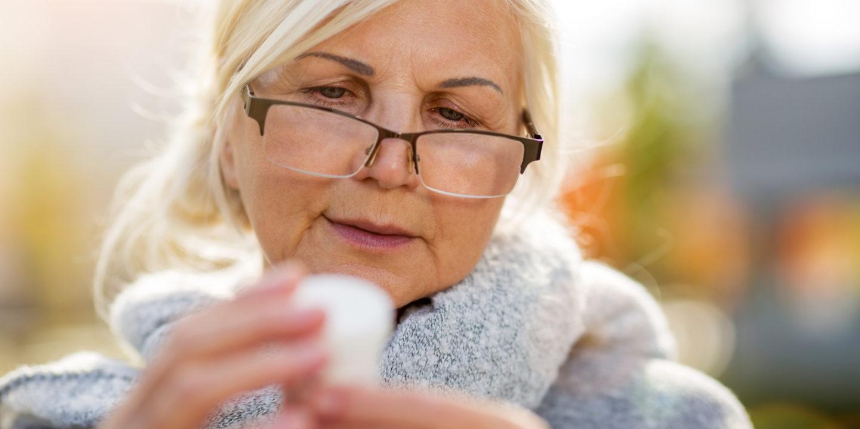 Elderly woman reading pill bottle