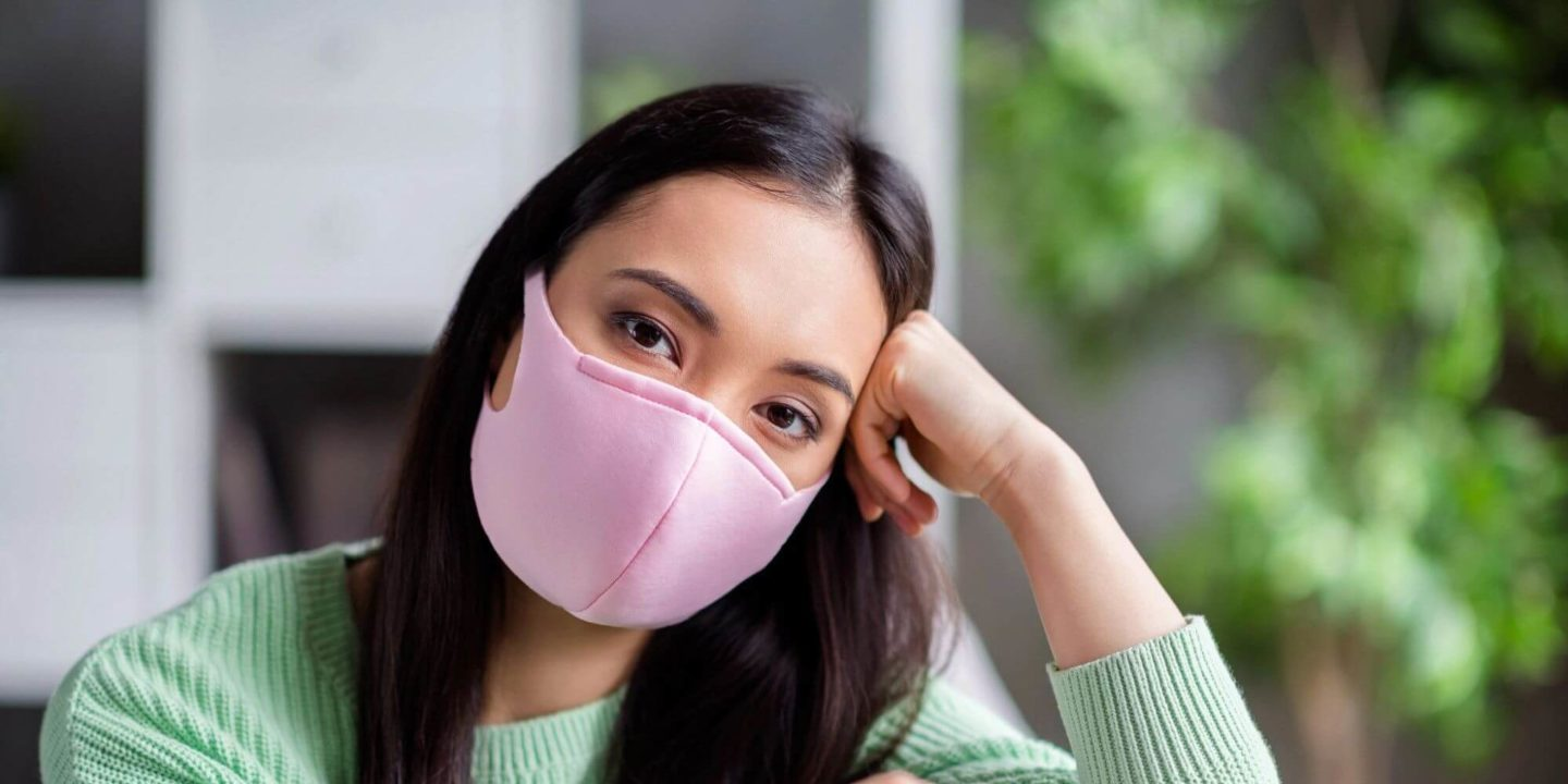 Woman wearing pink mask - Easing Back Into Public Places and Social Spaces | NSF International