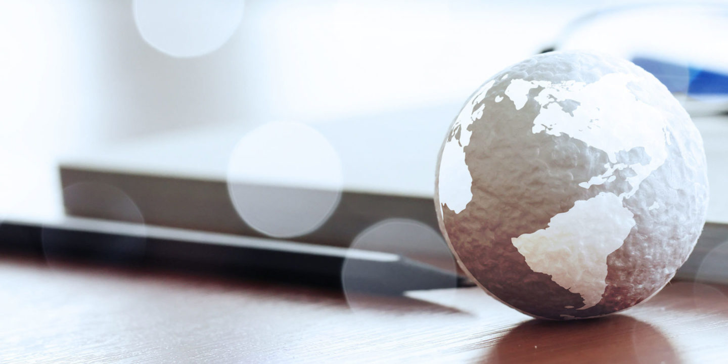 Globe on desk with pen, paper and glasses
