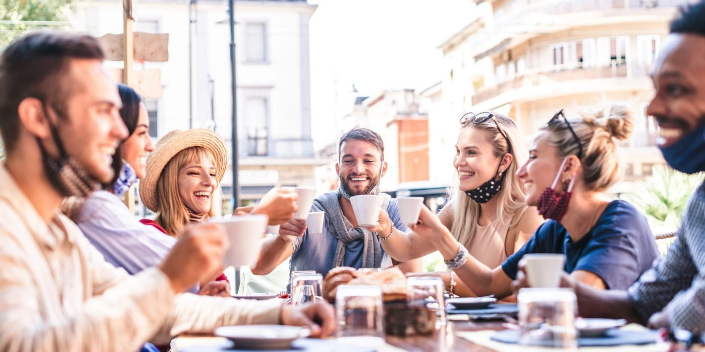 Group of people dining outdoors with masks - Canada's First COVID-19 Safety Ambassadors Help Local Businesses Reopen Safely   NSF International