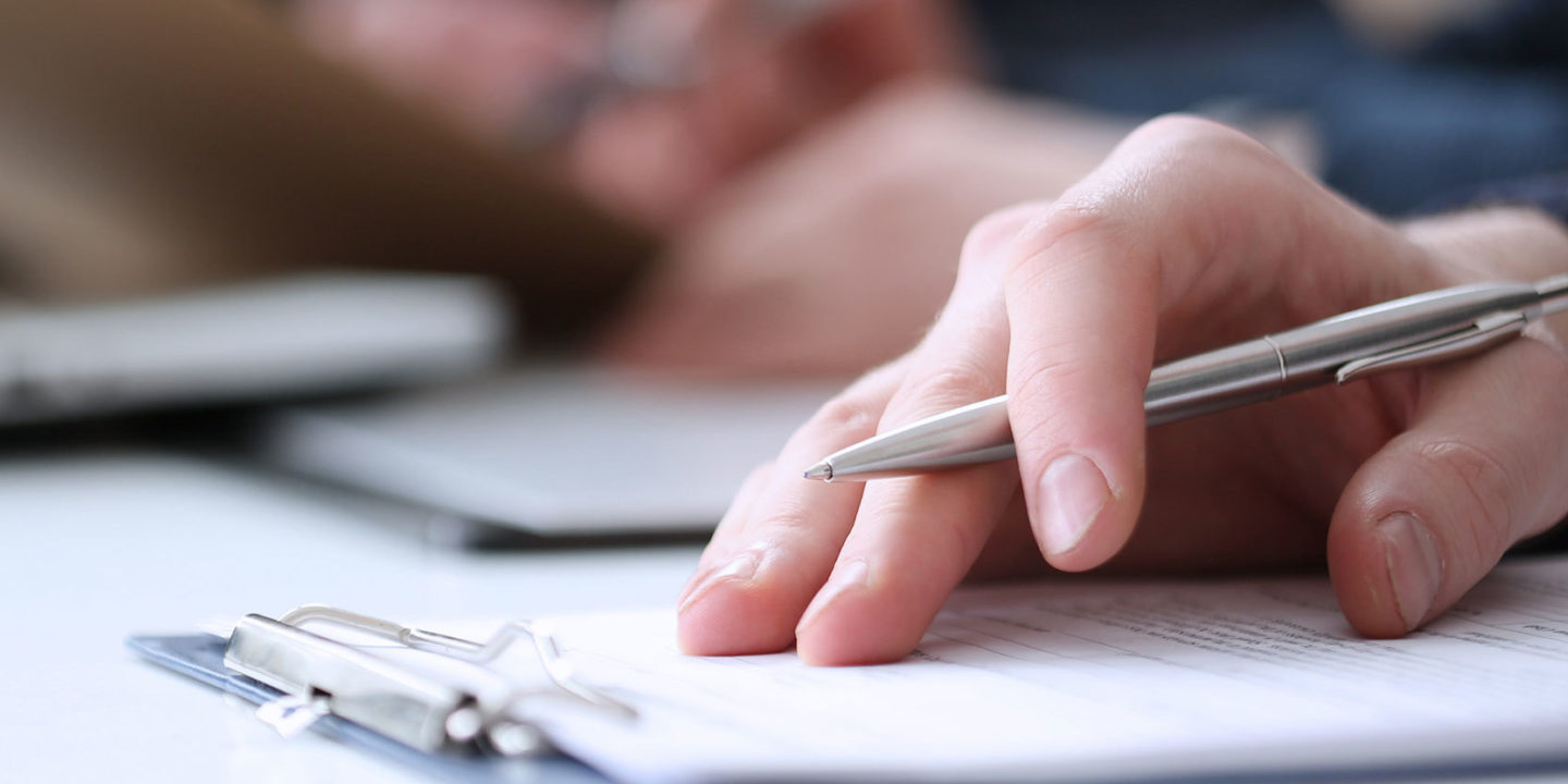 Hand with pen filling above clipboard - Complaints, Public Notices and Enforcement Actions   NSF International