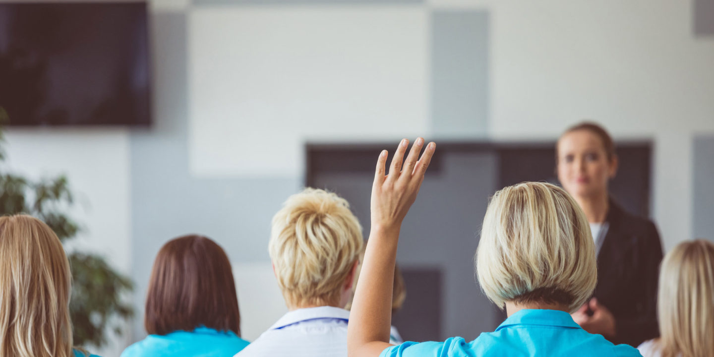 Training audience with woman raising hand