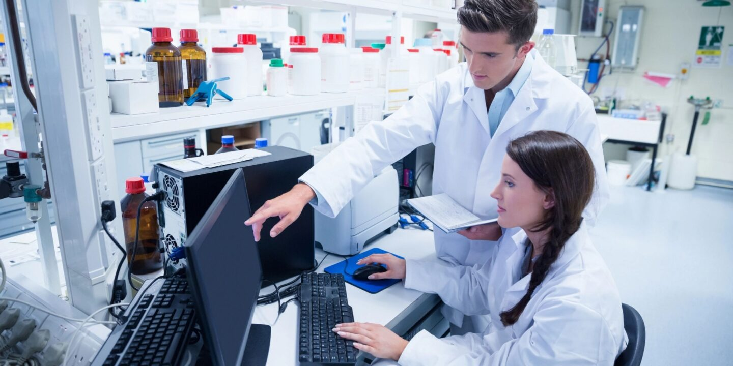 Two lab workers at computer station - Amarex Clinical Research to Manage Phase 2 Clinical Study of a New Therapy for COVID-19 Long-Haulers   NSF International