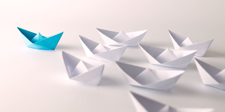 Blue paper ship leading among white
