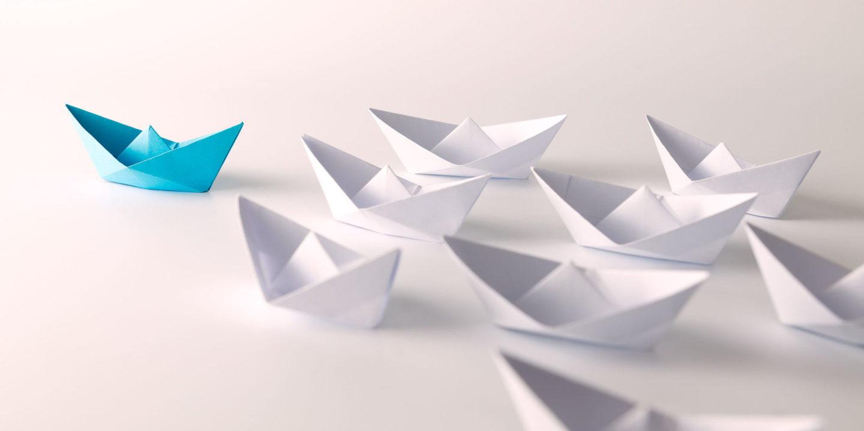 Blue paper ship leading among white - Leadership   NSF International