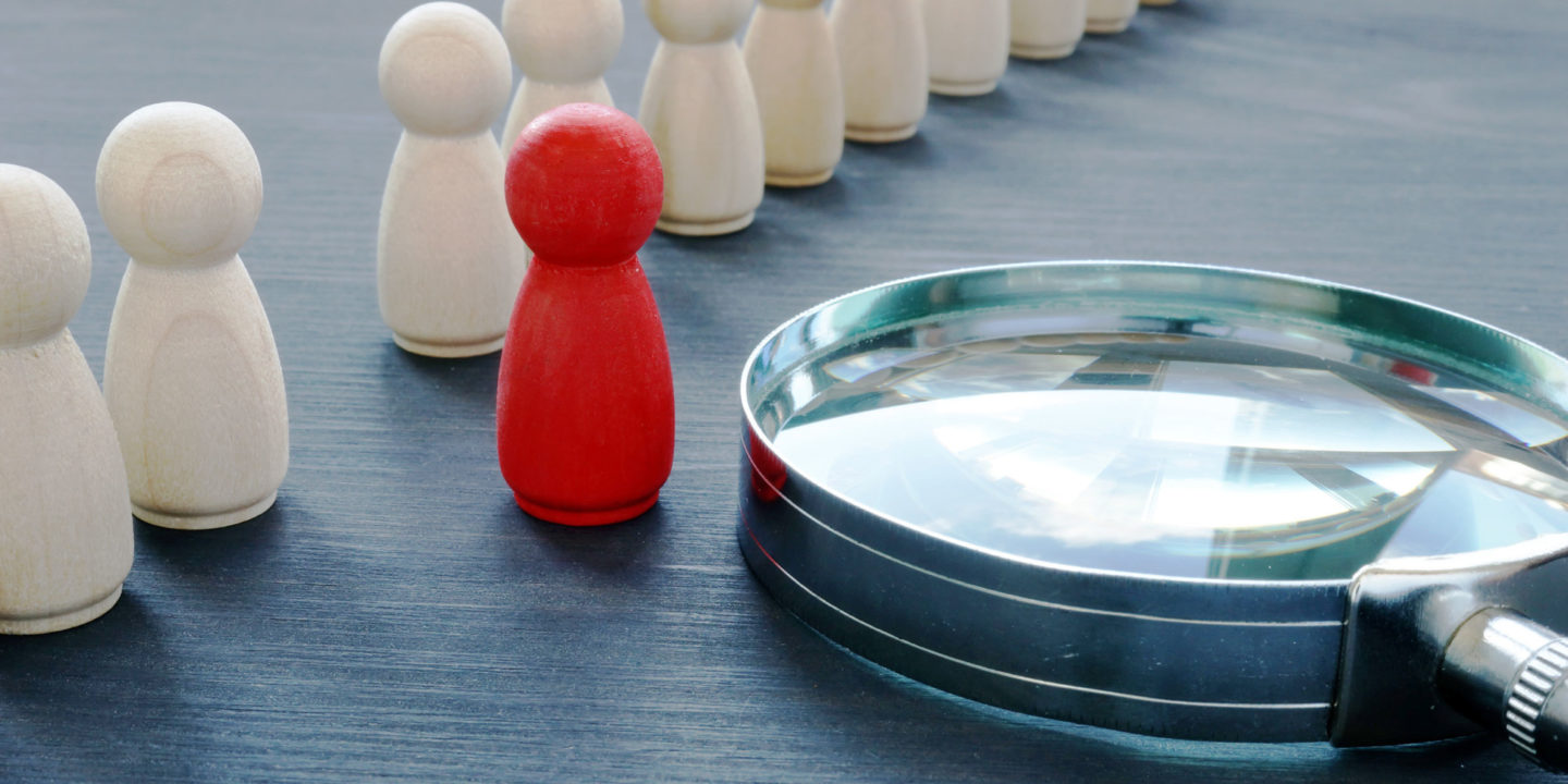 Red figurine standing out against white figurine next to magnifying glass