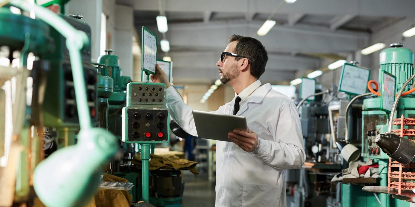 Man in factory reading screen at machine