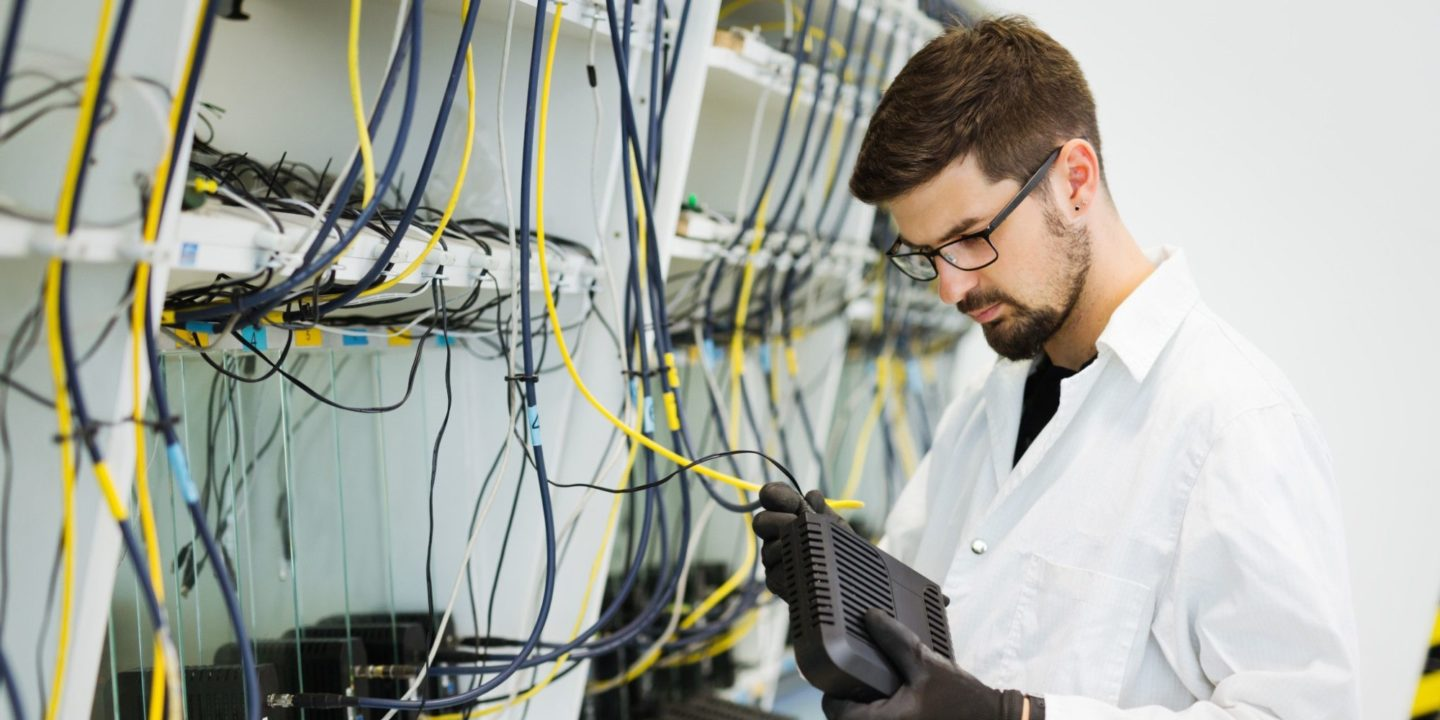 Man plugging in network wires - NSF-ISR's Provides Full ISO/IEC 27001 Certification Remotely   NSF International