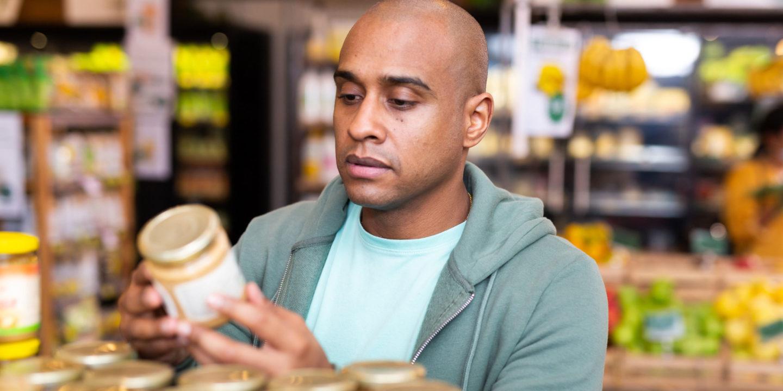 Man reading food label on a jar - Food Labeling   NSF International