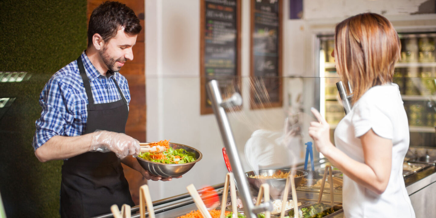Man with a beard making a salad for a customer at restaurant - Food Shield Certification Requirements   NSF International