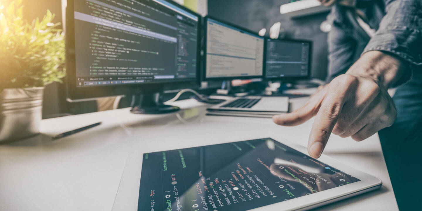 Man with tablet and security monitors - Eight Steps to the New Cybersecurity Maturity Model  Certification (CMMC) Now Required by the DoD   NSF International