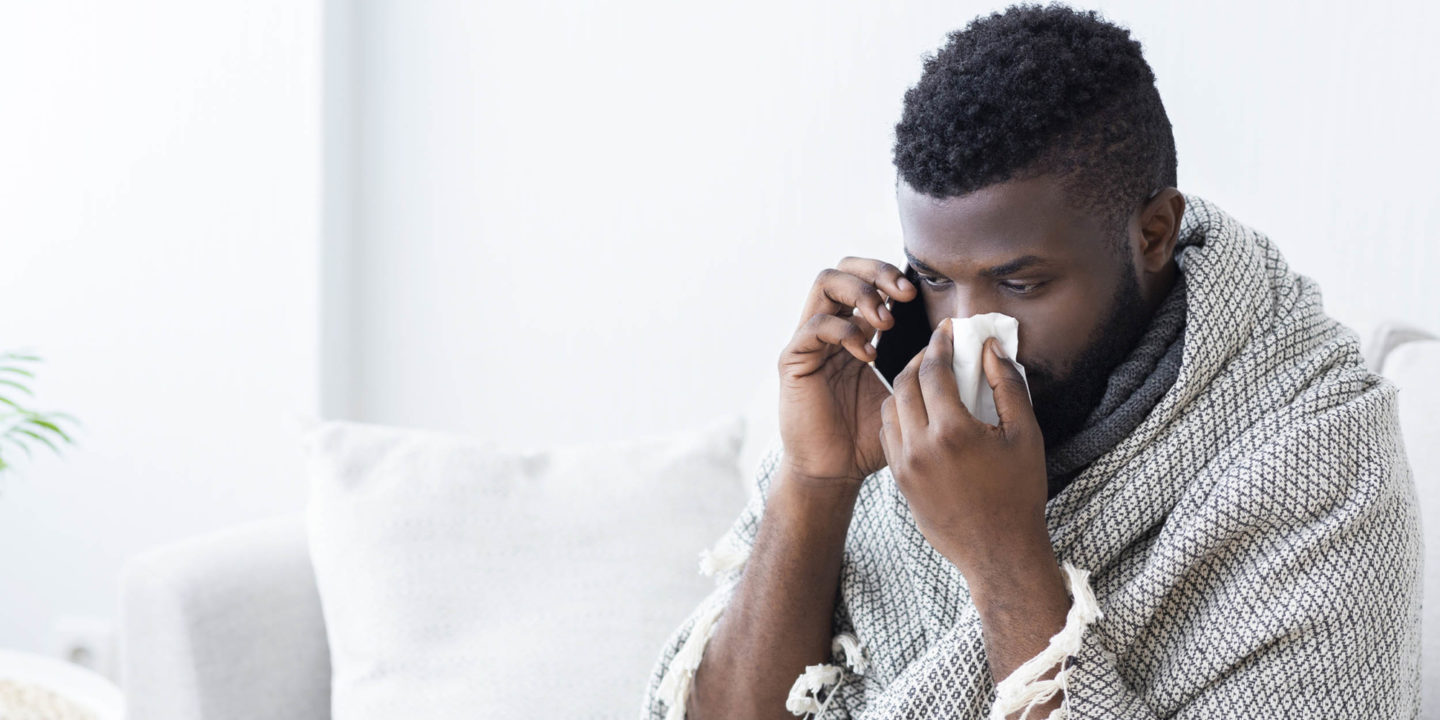 Man on phone with tissue covering his nose - Be a Flu Fighter: Protect Yourself From the Flu | NSF International