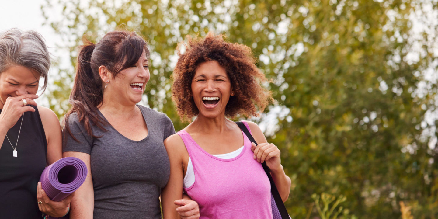 Group of mature female friends on outdoor yoga retreat walking along path.