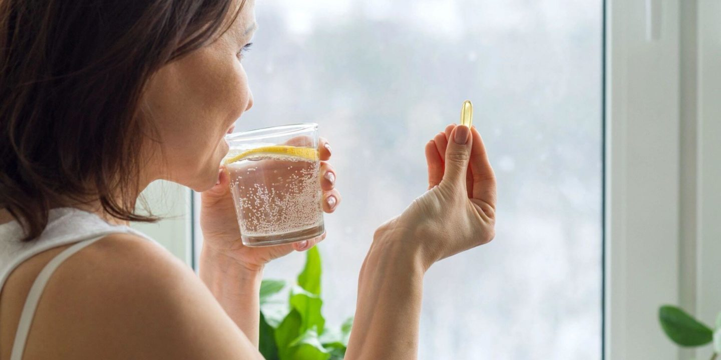 Woman taking natural supplement with lemon water - 5 Things You Need to Know About Taking Supplements Safely