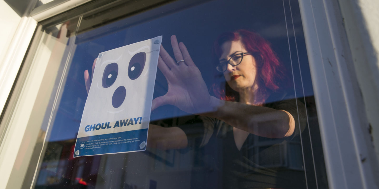 Woman hanging NSF Halloween poster in window