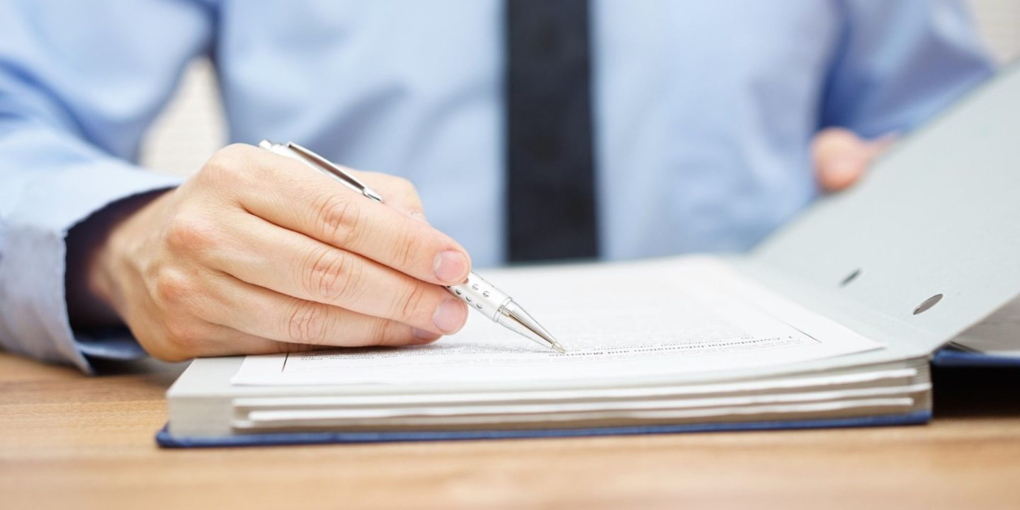 Man Pointing Pen at Wording on Paper - Purchase NSF Standards Documents | NSF International