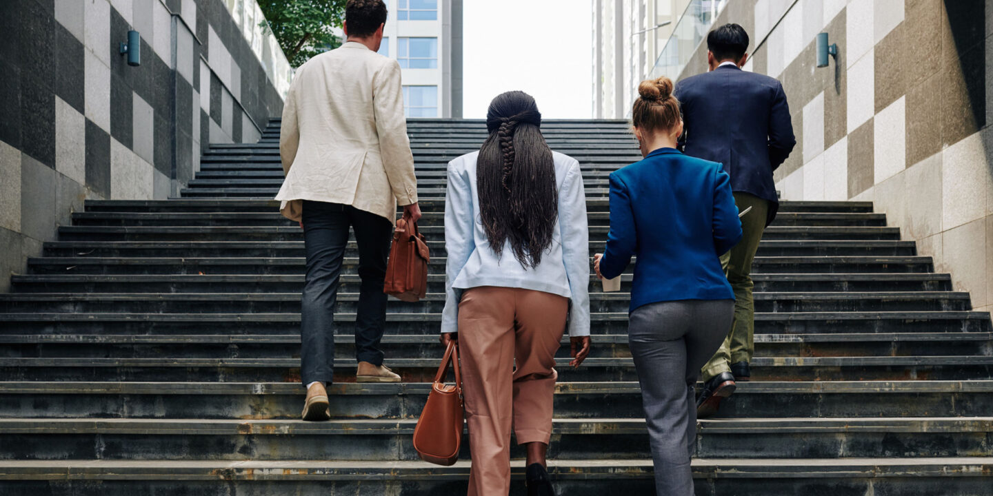 Group of people walking up stairs in city - A Guide to Cybersecurity Maturity Model Certification (CMMC) Levels | NSF International