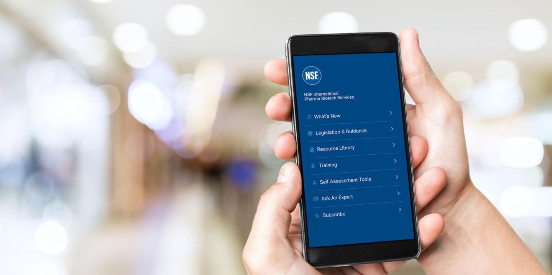 Hands holding up NSF Pharma app on mobile phone