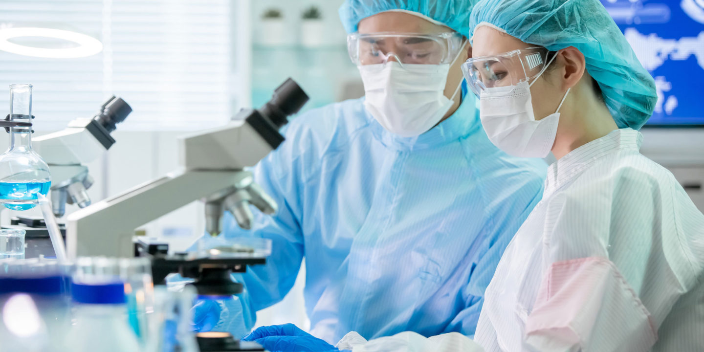 Male and female researchers dressed in scrubs in front of a microscope