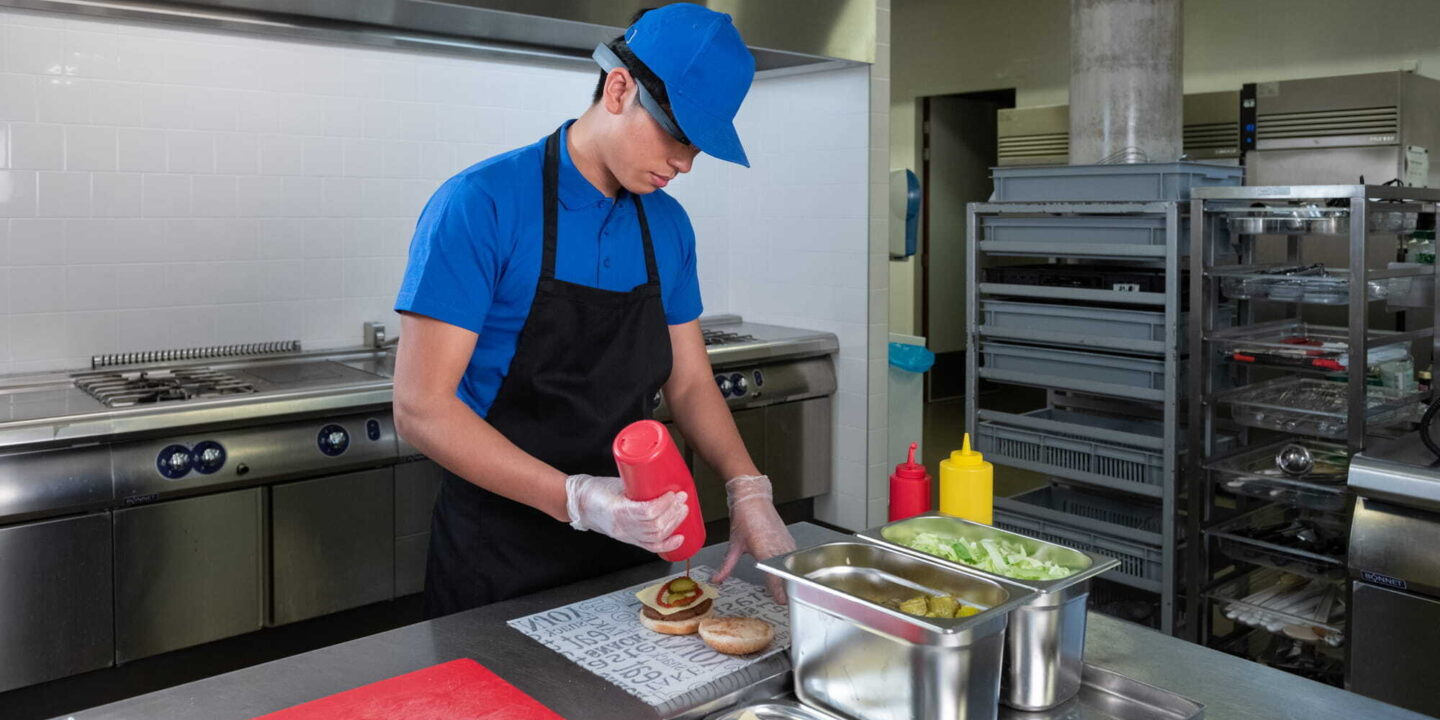 A restaurant worker adding sauce on burger patty - Wearable AR Technology for Food Service Industry   NSF International