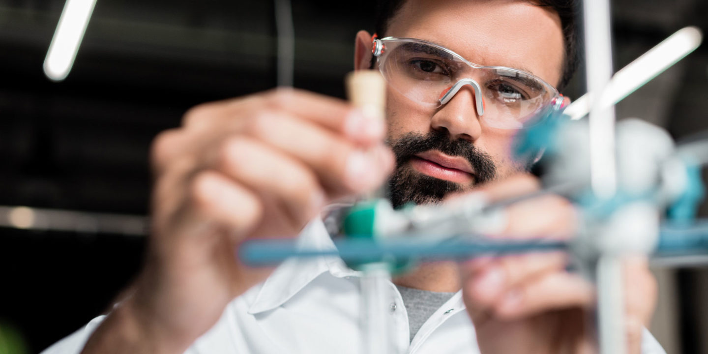 Scientist in protective eyewear making experiment in laboratory