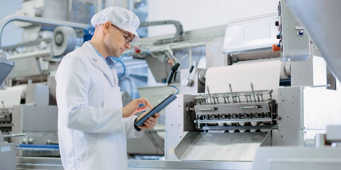 Male technician working with tablet in automated factory - What Makes a Lubricant a Food-Grade Lubricant   NSF international