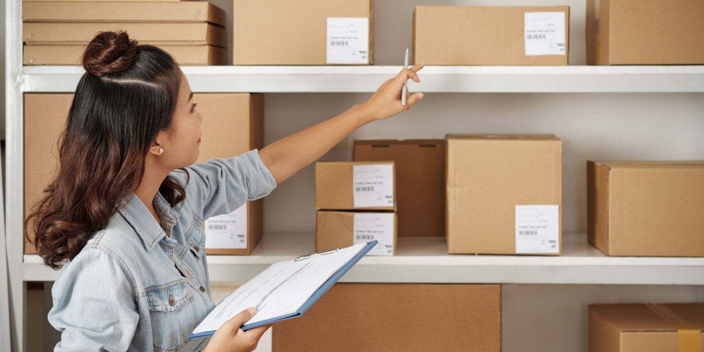 Women checking boxes on shelves Quality Management Systems (QMS) Certification