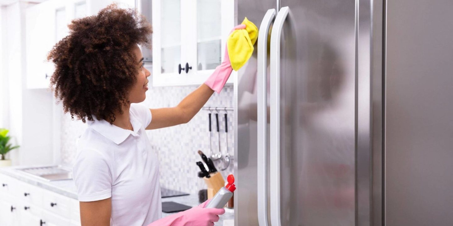 Woman cleaning refrigerator - Spring Cleaning to Feel Better and Create a Healthier Home | NSF International