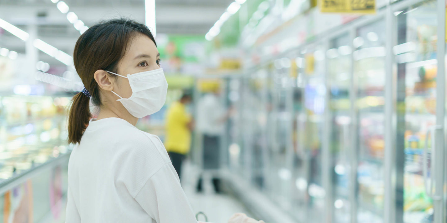 Woman grocery shopping while wearing a mask