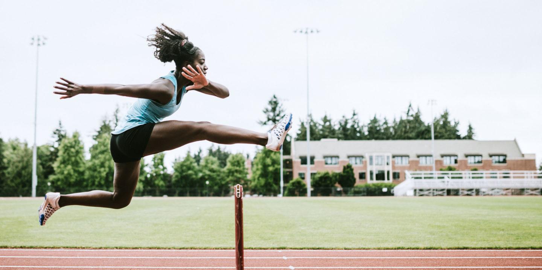 Woman jumping hurdle