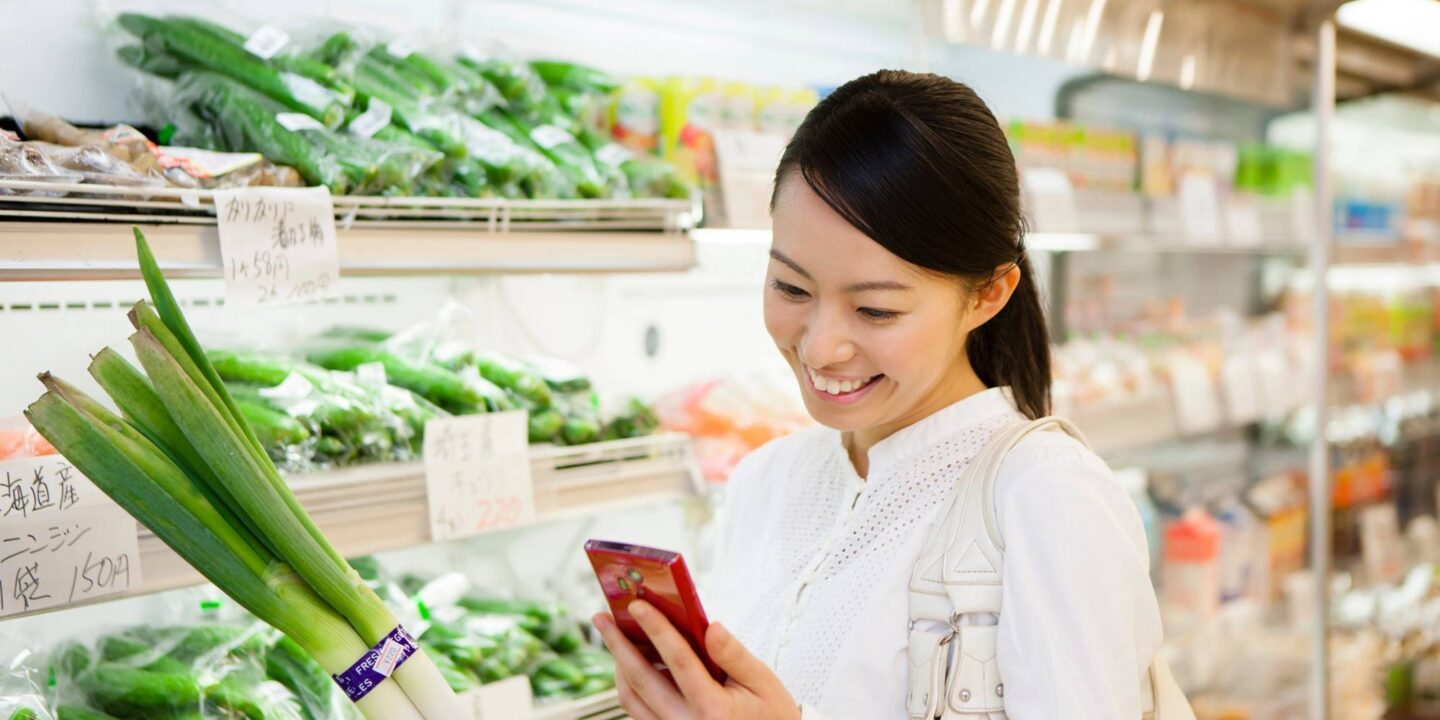 Woman looking at smartphone during grocery shopping - Three Tips to Shop for Plant-Based Food   NSF International