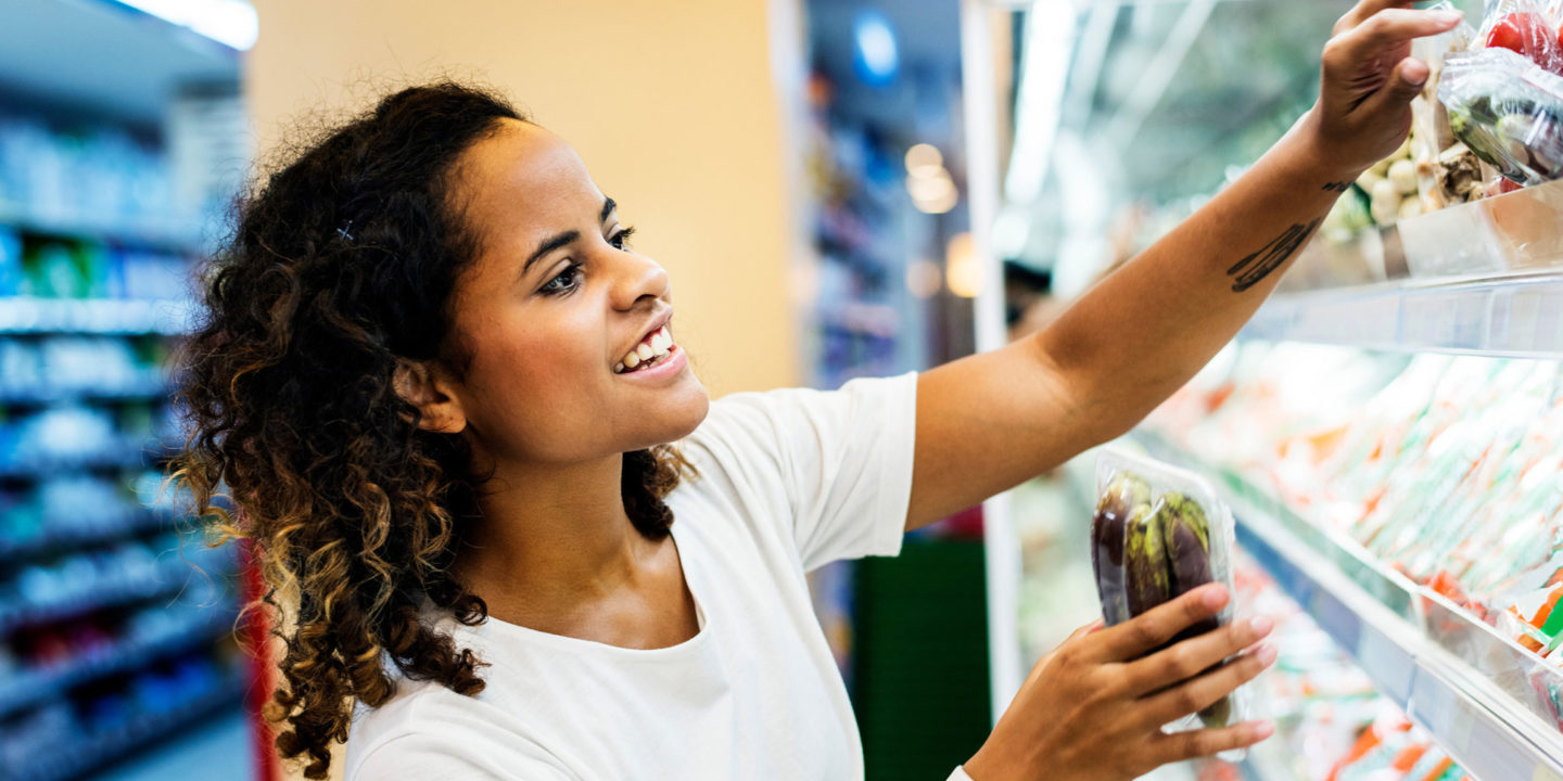 Woman shopping the refrigerated section at the supermarket