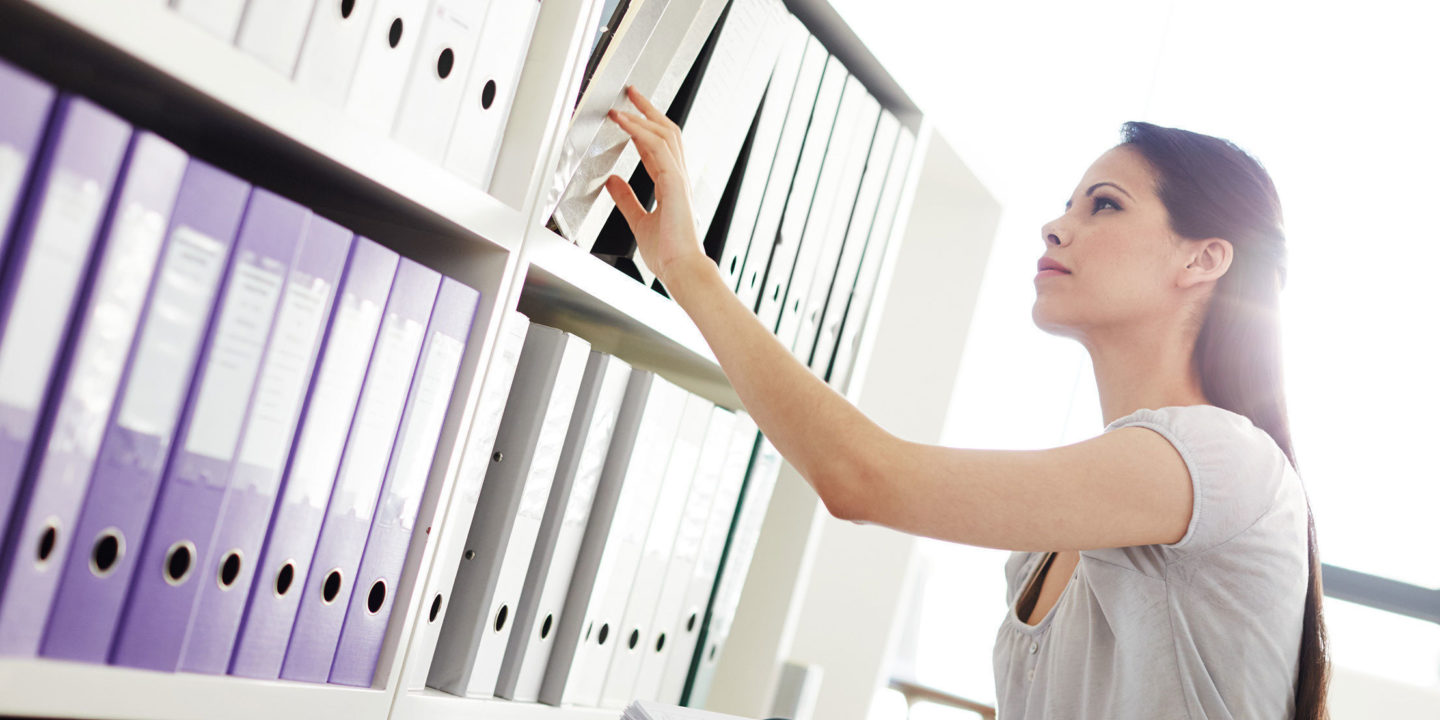 Young woman going through files on shelves in an office