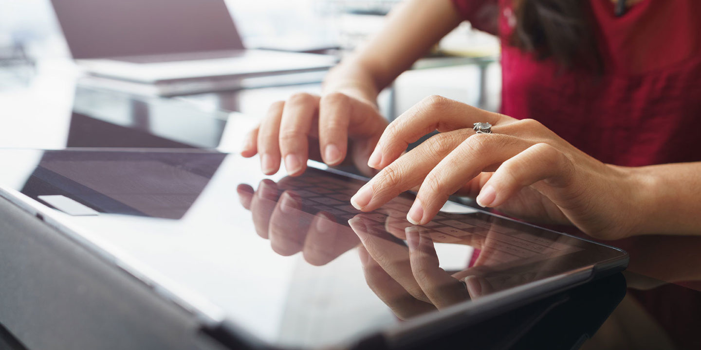 Closeup of female hands typing on tablet with laptop in background - Amarex Clinical Research Organization  NSF International