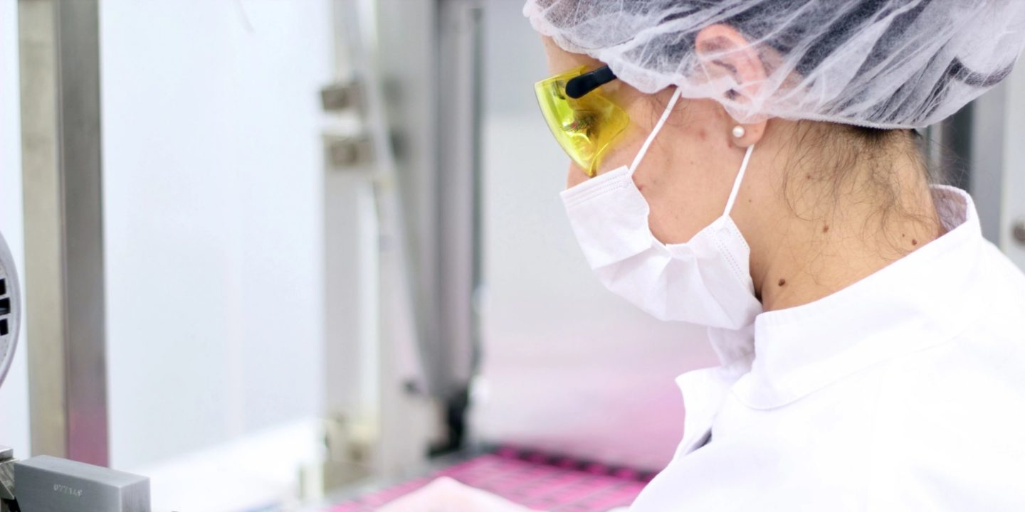 Female scientist with mask working in pharma company - Learning From A Successful GMP Remediation Program   NSF International