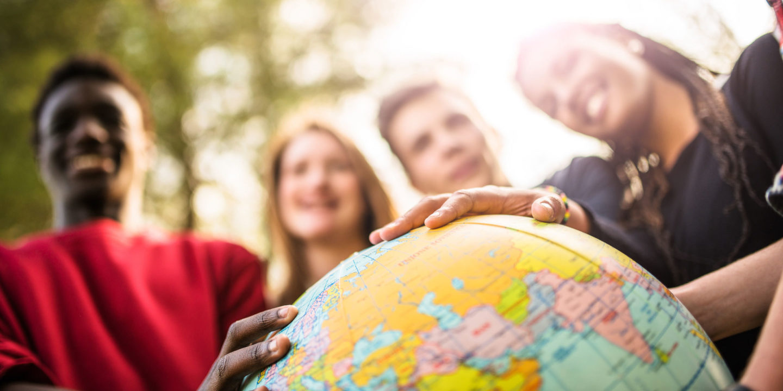 Young people smiling with globe - NSF International Companies   NSF International