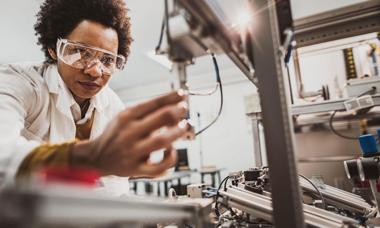 Lab worker examining machine parts