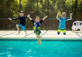 Young boys jumping into pool - Swimming Pool Safety Tips | NSF International