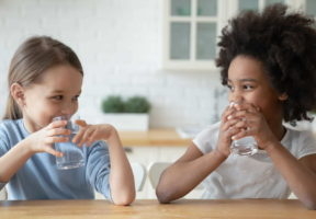 Smiling Little girls drinking pure mineral water - Water Well-being: Tips to Discover Lead in Your Drinking Water | NSF International
