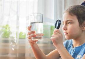 Girl looking at glass of water through magnifying glass - Bipartisan, NSF-Supported Legislation to Promote Clean Drinking Water | NSF International