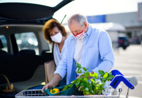 Older couple wearing masks loading groceries into vehicle