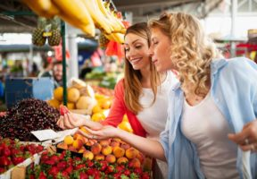 Happy young women shopping fruits in the market - Clear the Confusion About Organic and Non-GMO Food | NSF International