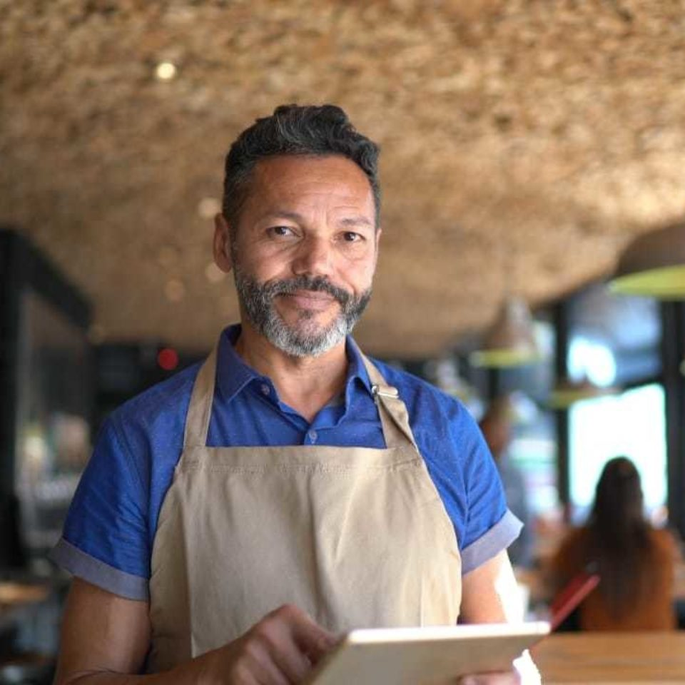 Man with tablet in restaurant - Leading You Forward   NSF International