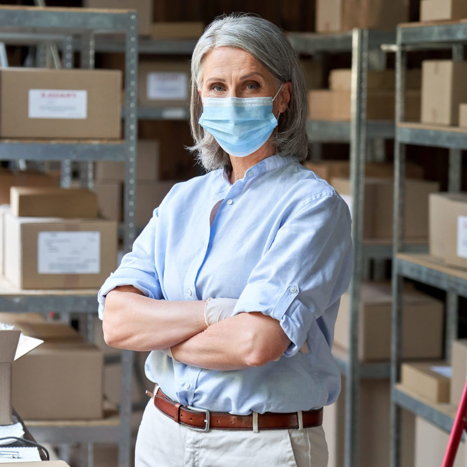 Woman wearing a mask in warehouse