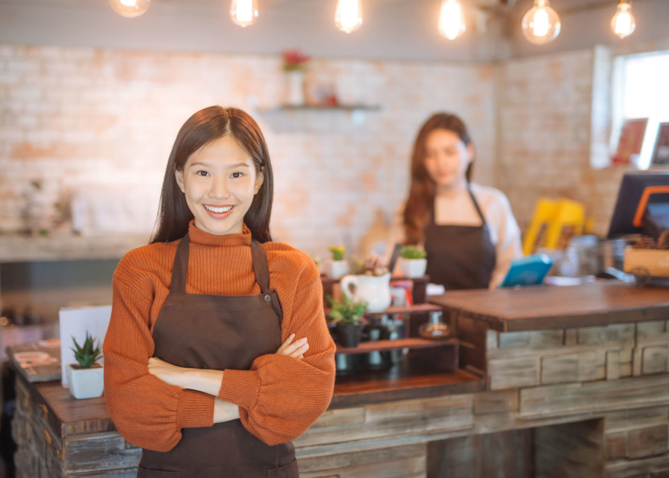 Asian restaurant owner with employee working in background