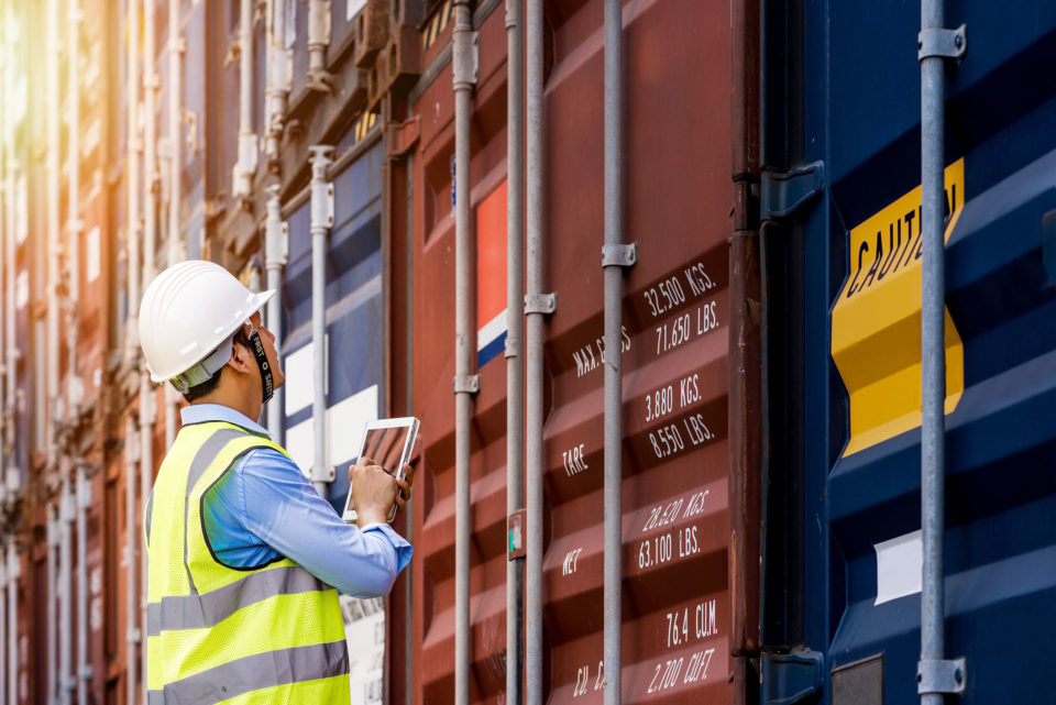Auditor checking containers  from cargo freight ship