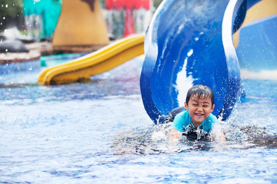 Boy coming down slide in pool