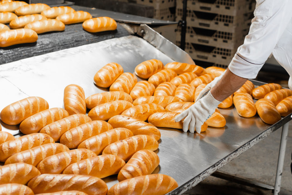 Baker taking bread off an automatic bread production line in a factory