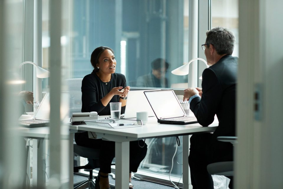 Business man and woman having discussion at desk